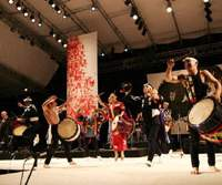 Members of Kodo perform at last year's Earth Celebration (above). Parades through the town of Ogi (below) are one of many ways that the festival has joined the local community.   MAIKO MIYAGAWA (above), CHRIS BRZOZOWSKI PHOTOS