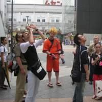 Tokyo's Akihabara district attracts tour groups for foreigners (above) led by the likes of Tokyo-based student Patrick W. Galbraith (left) who want to see geeks in their natural environment and be entertained by maid-clad waitresses but with authorities clamping down on otaku activity, manga and anime obsessives are beginning to look elsewhere for their virtual fun.   PATRICK MACIAS/ YOSHIAKI MIURA PHOTOS