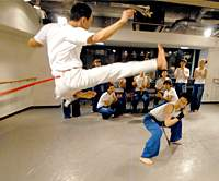 Capoeira instructor Ryuta Suda (above) shows how the dynamic Afro-Brazilian martial art is done at a class in Hamamatsucho, while students provide the traditional musical accompaniment.