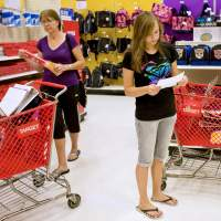 Careful spending: A teenage girl looks at a list as she shops for school supplies at a Super Target store in Littleton, Colorado. One of the key life skills experts say kids need to learn early is managing a budget. | BLOOMBERG