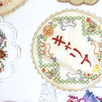 Embroidered works by Ruri Clarkson, including one that has the word 'kyaria,' meaning 'career,' stitched in the center.