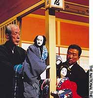 Tamao Yoshida (left) operating the puppet of Chubei, and Minosuke Yoshida operating Umegawa in Act Two of'The Couriers of Love'