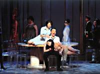 Guido (Kiichi Fukui), the lone male character in 'Nine,' receives the attentions of his wife Luisa (Katsura Takahashi) as she sits on the table, and his mistress Carla (Yukiko Ikeda) as she lies sprawled across his legs.