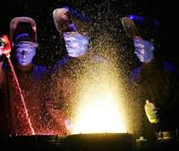 A spray of paint bursts from a drum as Blue Man Group perform one of their routines. | © BMP