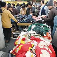 Shoppers examine old kimono and used clothes (above) at the Setagaya Boroichi flea market in Tokyo, which attracts around 800,000 people searching for antiques to craft goods to bric-a-brac. | YOSHIAKI MIURA PHOTOS
