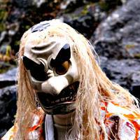 A local wears a mask and costume used in the yokagura dance for the benefit of tourists.