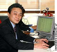 Yasunori Fujikura, president of TraBox Inc., shows off the firm's online clearing house program for truckers at his office in Shibuya Ward, Tokyo.