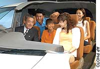 Honda Motor Co. President Takeo Fukui (left) poses with models in a skeleton model of the automaker's new Edix minivan during a media preview.