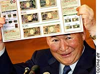 Bank of Japan Gov. Toshihiko Fukui displays a catalog of new bank notes during a news conference in Tokyo. The new bank notes will be issued around November.