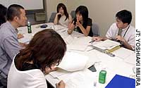 Noriko Nomura (second from right) and other members of a Nissan Motor Co. task force discuss ways to attract female car-buyers at the firm's head office in Tokyo's Ginza district.