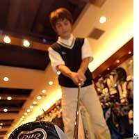 A store clerk demonstrates a driver at a Victoria Golf store in Tokyo's Minato Ward.