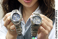 A Casio Computer Co. employee displays a G-Shock model (left) and another radio-controlled watch.