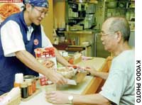 A customer is served 'gyudon' beef-on-rice with Australian meat at a Sukiya eatery Friday in Tokyo's Minato Ward on the first day the dish was put back on the menu.