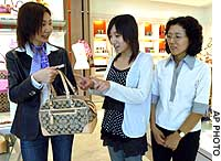 A Coach saleswoman shows a bag to customer Akiko Yamaguchi (center) and her mother, Yumiko, at the company's store in central Tokyo.