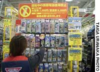Kawasaki, Kanagawa Pref. -- A store employee shows the different types of hands-free devices for cell phones at Super Autobacs Kawasaki on Thursday.