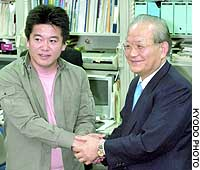 Livedoor Co. President Takafumi Horie (left) and Saikyo Bank President Mitsuhiro Ohashi pose during a news conference in Tokyo.
