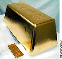 The world's largest gold bar, made by Mitsubishi Materials Corp., at 250 kg is compared with the manufacturer's 1 kg gold plate in this company-supplied photo.