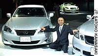 Toyota Motor Corp. President Katsuaki Watanabe poses with remodeled Lexus cars during a news conference Tuesday in Tokyo.