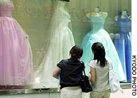 Women look at wedding dresses at a shop in Tokyo.