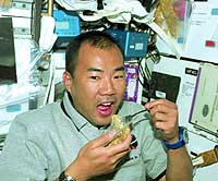 Astronaut Soichi Noguchi slurps a package of instant noodles specially developed for space travel by Nissin Food Products Co. | JAPAN AEROSPACE EXPLORATION AGENCY PHOTO/KYODO