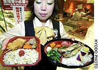 An employee at Hanshin Department Store in Osaka displays on Monday two types of 'bento' boxed lunches based on popular menus from World War II.