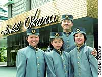 Children in Hotel Okura Tokyo uniforms hang out with an employee near the entrance.
