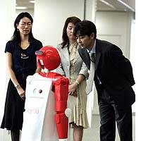 A Fujitsu Ltd. employee responds to an enon robot during a Tuesday demonstration in Tokyo as other employees look on.