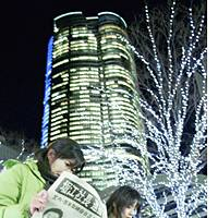 Women read an extra newspaper edition Monday night in Tokyo reporting the arrest of Livedoor Co. founder Takafumi Horie, whose home and headquarters are in the Roppongi Hills complex looming behind them.