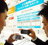 Shoppers check out NTT DoCoMo mobile handsets equipped with TV tuners at a Bic Camera store in Tokyo's Yurakucho district Thursday.