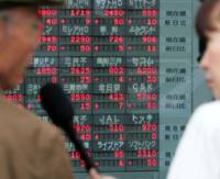 A tv reporter interviews a passerby in front of a stock quotation board in Tokyo on Thursday, the last day of trading for Livedoor Co., which will be delisted Friday.