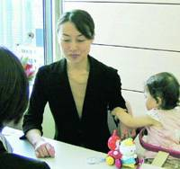 A woman brings her child to a job consultation at Fuji Staff Inc. temp agency in Tokyo's Shinjuku Ward, which offers a child-care service.