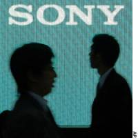 People pass by a monitor displaying Sony Corp.'s logo at the Sony Building Thursday in Tokyo.