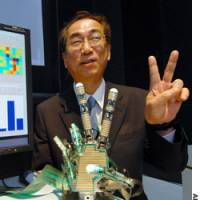 Honda Research Institute Japan Co. President Tomohiko Kawanabe flashes a V sign as he demonstrates a new robot technology in Tokyo.