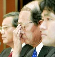 Akio Okuyama (center), chairman of the board of ChuoAoyama PricewaterhouseCoopers, faces reporters in Tokyo on May 10 about the business suspension order the government issued to the auditing firm.