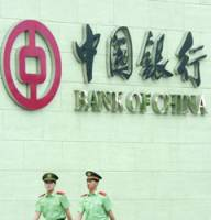 Security officials walk in front of the Bank of China's head office here Thursday, the day it went public on the Hong Kong Stock Exchange.