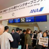 Passengers line up to board an All Nippon Airways flight to Shanghai in the renovated South Wing of Narita International Airport's Terminal 1 on opening day, Friday.