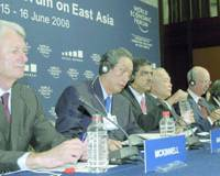 Kunio Nakamura (second from left), president of Matsushita Electric Industrial Co. and cochair of the World Economic Forum on East Asia, speaks to reporters Thursday before the start of the conference.