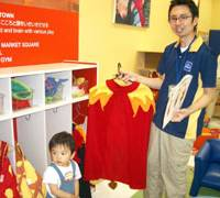 Hiroshi Tsutsui, manager of the Yokohama outlet of indoor play center chain KID-O-KID, displays a costume for kids.