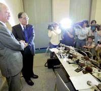 Hankyu Holdings Inc. President Kazuo Sumi (left) and Shinya Sakai, Hanshin Electric Railway Co.'s next president, join hands for the cameras Tuesday morning during a news conference at Hankyu headquarters in Kita Ward.