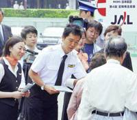 Japan Airlines employees pass out fliers to people heading to the carrier's general shareholders' meeting in Chiyoda Ward, Tokyo, on Wednesday. | KYODO PHOTO
