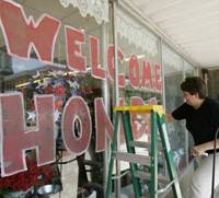 Susan Rust paints 'Welcome Honda' Wednesday on the front of her store in downtown Greensburg, after the carmaker announced it will build a plant near the city.   AP PHOTO