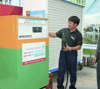 An employee at Aburato Shoji Corp.'s gas station in Toyosato, Shiga Prefecture, tells a customer about its program to turn used vegetable oil into biodiesel. | KYODO PHOTO