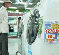 A shopper looks at Toshiba Corp.'s new washer-dryers that have a cooling function last week at a home appliance store in Chiyoda Ward, Tokyo. | KYODO PHOTO