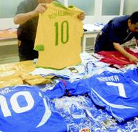 Customs officials show off counterfeit World Cup soccer jerseys seized in June.   KYODO PHOTO