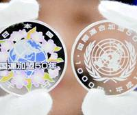 A pair of 1,000 yen silver coins commemorating the 50th anniversary of Japan's entry into the United Nations are shown to reporters Wednesday in Osaka.   KYODO PHOTO