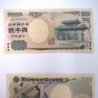 The 2,000 yen bank note depicts Shureimon Gate in Okinawa Prefecture on the front and a scene from 'The Tale of Genji,' the classic Japanese novel written in the early 11th century, on the back. | KYODO PHOTO