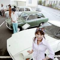 Models pose in Nissan Motor Co.'s classic car display at the firm's factory in Yokohama on Wednesday. | KYODO PHOTO