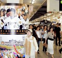 Passengers walk past a poster of the Hanshin Tigers at Hankyu Umeda Station on Monday. Hankyu Holdings Inc. and Hanshin Electric Railway Co. began putting up advertisements at the station for the Tigers and Hankyu-owned Takarazuka Revue Co., ahead of the merger of the two former rival companies on Oct. 1. | KYODO PHOTO