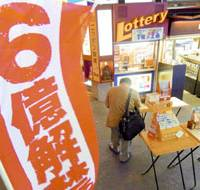 A passerby checks out the new BIG soccer lottery Sept. 16 at a kiosk in Tokyo's Marunouchi district.   KYODO PHOTO