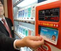 An employee of the Tobacco Institute of Japan holds up an IC card that allows only those with the card to buy cigarettes from vending machines, during a demonstration for the media Thursday in Tokyo. | YOSHIAKI MIURA PHOTO